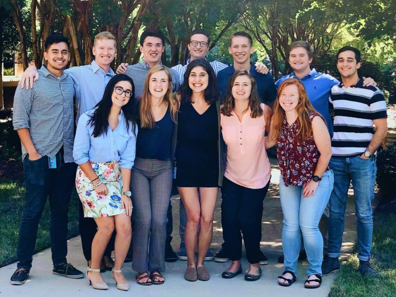 Group photo of an internship class, outside standing under the trees